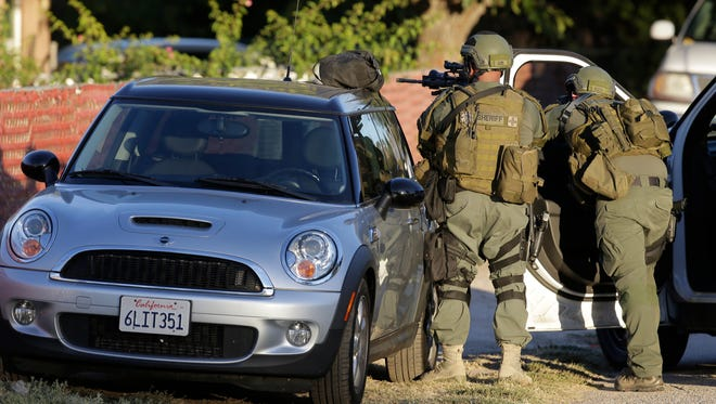 Law enforcement search for a suspect in a mass shooting that occurred at a Southern California social services center on Wednesday, Dec. 2, 2015, in San Bernardino, Calif. One or more gunmen opened fire Wednesday at a California center that serves people with developmental disabilities, shooting several people as others locked themselves in their offices, desperately waiting to be rescued by police, witnesses and authorities said.