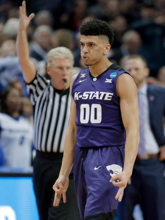 Kansas State's Mike McGuirl (00) reacts to making a basket against Creighton during the first half of a first-round game in the NCAA men's college basketball tournament in Charlotte, N.C., Friday, March 16, 2018. (AP Photo/Bob Leverone)