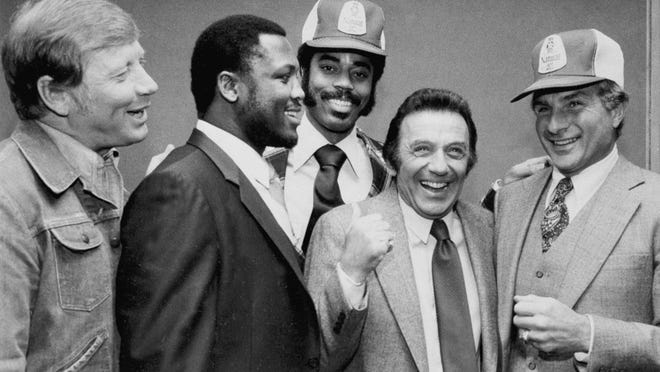 In this March 1980 file photo, comedian Norm Crosby, second from right, gives a thumbs-up as he is surrounded by sports figures, from left, Mickey Mantle, Joe Frazier, Walt Frazier and Nick Buoniconti in New York, to launch a new ad campaign for a light beer. Crosby, the deadpan mangler of the English language who thrived in the 1960s, þÄô70s  and þÄô80s as a television, nightclub and casino comedian, has died. He was 93. CrosbyþÄôs daughter-in-law, Maggie Crosby, told the New York Times that the comic died Saturday, Nov. 7, 2020 of heart failure in Los Angeles.
