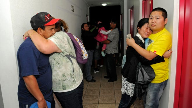 People embrace on the upper floor of an apartment building located a few blocks from the coast where they gathered to avoid a possible tsunami after an earthquake in Iquique, Chile, Tuesday.