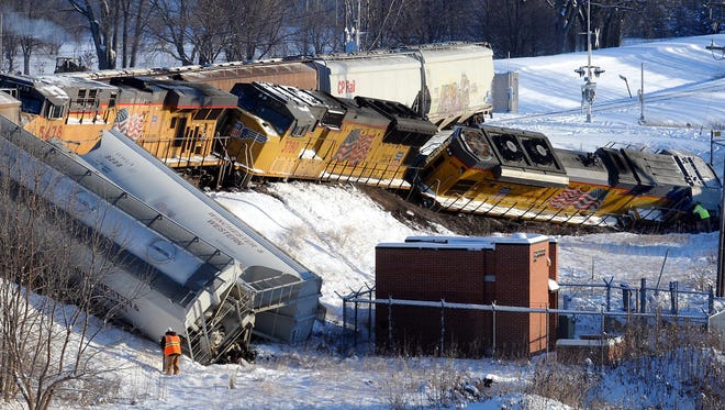 A Union Pacific worker stands at the site of a train derailment on the southwest edge of Mankato on Thursday. Several engines and grain cars left the the tracks at about 2:30 a.m. There were no injuries.