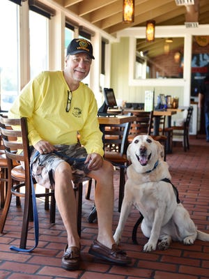 Veteran Carl Ray Furr sits with his service dog, Blanca, at Chili's Grill and Bar in Jackson on Thursday. A day before, Furr alleges he was asked to leave Scrooge's in Jackson because they said Blanca's behavior was agressive.