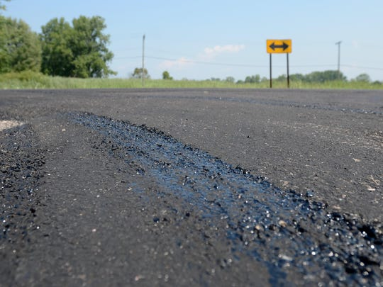 Tar bubbles to the surface of the road Monday, Aug 17, at the corner of La Croix Road and Green Drive on Harsens Island.
