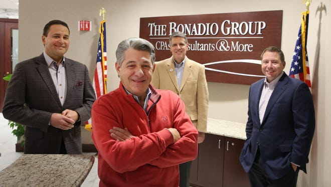Tom Bonadio, CEO, front center, stands with his managers, from left, Bruce Zicari, practice leader for small business advisory and CEO elect, Mario Urso, Chief of Board of Directors, and Bob Enright, COO, at the Bonadio Group, a Top Workplace last year.