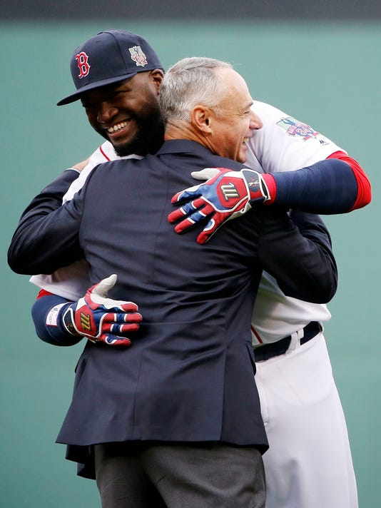 Boston Red Sox's David Ortiz hugs Baseball Commissioner Rob Manfred during a ceremony to honor Ortiz before a baseball game against the Toronto Blue Jays in Boston, Sunday, Oct. 2, 2016. (AP Photo/Michael Dwyer)