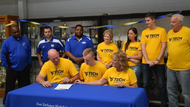 Family and coaches look on as Fort Defiance's Josh Whelan, center, his mother, Amy, right, and father, Shawn, left, sign his letter of intent to play basketball at West Virginia University Tech on Friday, Nov. 3, 2017, at Fort Defiance High School in Fort Defiance, Va.
