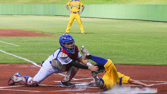 In this file photo, Taichung Sunflower's Lin Ya Wen dodges the tag and dives for home plate to score a run during the inaugural Guam Women's Baseball Cup opening game against the Taipei Vanguard at the LeoPalace Resort in Yona on Aug. 11.