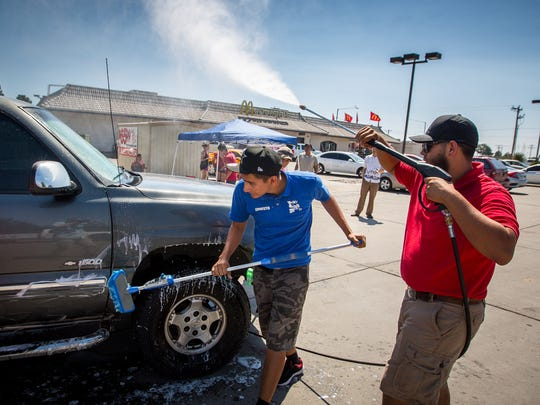 Ernesto Rosas, center, and Israel Vasquez try to stay cool while washing cars off of Avenida de Mesilla during a fundraiser for the Las Cruces Rescue Team, a group dedicated to providing volunteer opportunities for southern New Mexico, June 18, 2016.