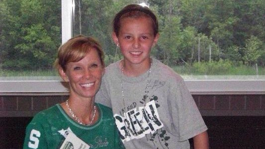 Claire Hendrickson of Wyoming, Mich., poses as a fourth-grader with MSU basketball coach Suzy Merchant. Hendrickson committed to play for the Spartans in 2017.