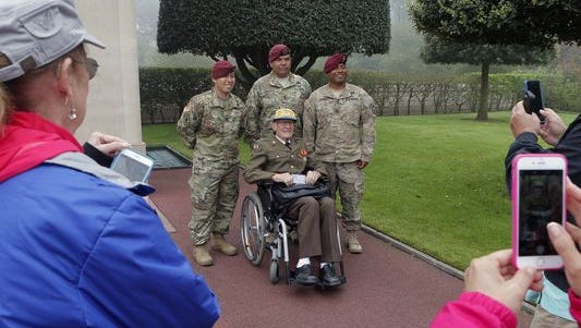 U.S. Air Force veteran Hartley Baird of Pittsburgh, who sailed into Normandy in August 1944 poses for visitors flanked by U.S. soldiers from Jber, Alaska, in the Colleville American military cemetery, in Colleville sur Mer, France, on Monday, the 72nd anniversary of the D-Day landings.