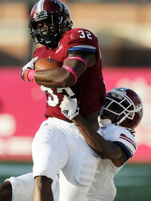Troy University's Brandon Burks (32) is stopped by New Mexico State's Lewis Hill (29) at Veterans Memorial Stadium in Troy, Ala. on Saturday October 11, 2014.