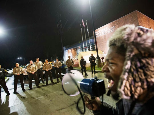 Protester Derrick Robinson shouts through a bullhorn at police officers standing guard during a demonstration outside the Ferguson Police Department, Sunday, Nov. 23, 2014, in Ferguson, Mo. Ferguson and the St. Louis region are on edge in anticipation of the announcement by a grand jury whether to criminally charge Officer Darren Wilson in the killing of 18-year-old Michael Brown. (AP Photo/David Goldman)