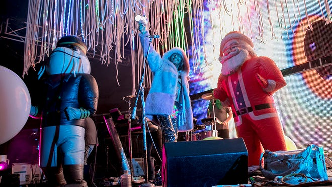 Wayne Coyne of The Flaming Lips and an inflatable Santa Claus share a stage at the Arizona State Fair.
