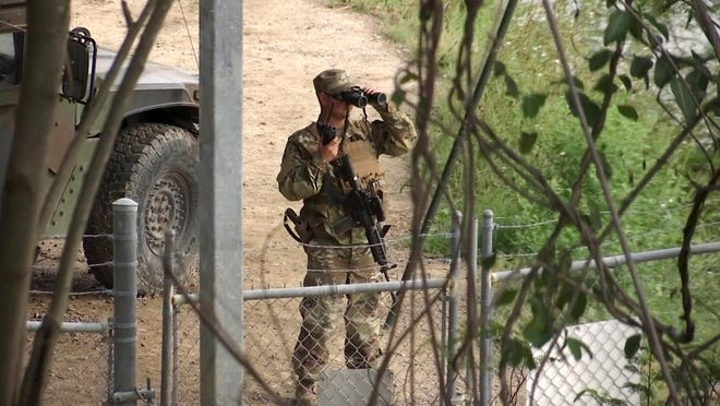 A National Guardsman watches over the Rio Grande in Roma, Texas, in an April 10, 2018, photo. The deployment of the National Guard to the U.S.-Mexico border is meant to curb illegal immigration.