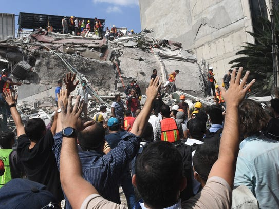 Rescuers search for survivors amid the rubble of a