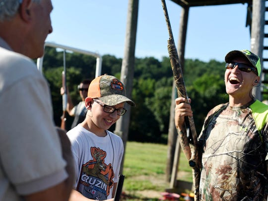 Cruz Mead, 15, center, and his dad Mike Mead, right, joke with fellow clay bird shooters at Starview Sportsmen's Club. Mead began teaching Cruz firearm safety when he was four years old, beginning on a suction cup gun.