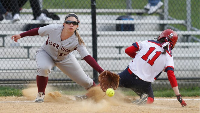 Harrison third baseman Christina DeCarlo (16) reaches for a throw as Eastchester's Sophia Tiso (11) slides in to the third base during a varsity softball game at Harrison High School on Thursday, April 28, 2016.