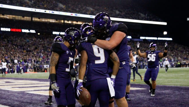 Teammates celebrate with Washington Huskies running back Myles Gaskin (9) after he scored on a 8-yard touchdown run against the California Golden Bears during the first half at Husky Stadium.