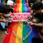 Filipino members of the LGBT community light candles during a vigil to pay tribute to the victims of the Orlando, Fla. mass shooting Tuesday, June 14, 2016 at the University of the Philippines campus in suburban Quezon city northeast of Manila, Philippines.