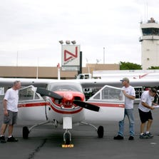 Bob Maxwell (left) watches as mechanic Jon Thompson (in hat) and avionics manager Danny Pinson work on Maxwell's prop plane at Falcon Field.