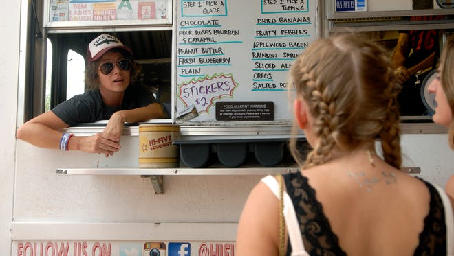 Leslie Wilson of High-Five Donuts talks with a customer at the 2016 Forecastle Festival on Waterfront Park.  July 15, 2016