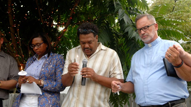 Nicole Yates, of the New Albany NAACP, left, Mark Henderson, center, and Rev. Rick Kautz, right, pray together at the Unity Rally in New Albany's ESNA Neighborhood Park on Tuesday, Aug. 15, 2017.