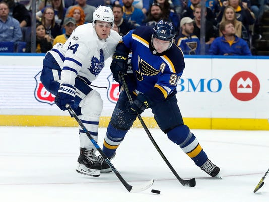 St. Louis Blues' Vladimir Tarasenko, of Russia, reaches for the puck as Toronto Maple Leafs' Auston Matthews, left, defends during the second period of an NHL hockey game Saturday, Nov. 4, 2017, in St. Louis. (AP Photo/Jeff Roberson)