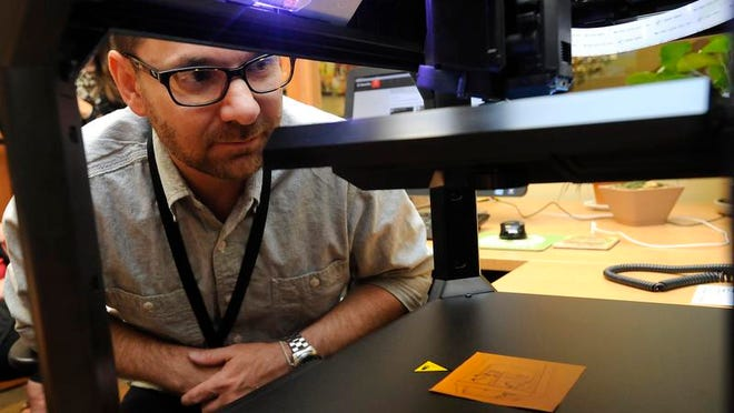 John Dyer, teen librarian at the Donald W. Reynolds Library, watches as a 3-D printer creates a cube. The library is one of the first in the state to feature the technology.