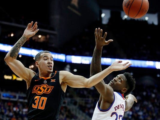 Oklahoma State's Jeffrey Carroll (30) and Kansas' Silvio De Sousa (22) chase a rebound during the first half of an NCAA college basketball game in the Big 12 men's tournament Thursday, March 8, 2018, in Kansas City, Mo. (AP Photo/Charlie Riedel)
