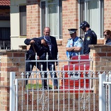 Forensic experts collect evidence from a house in the Guildford area of Sydney, Australia, on Sept. 18, 2014.
