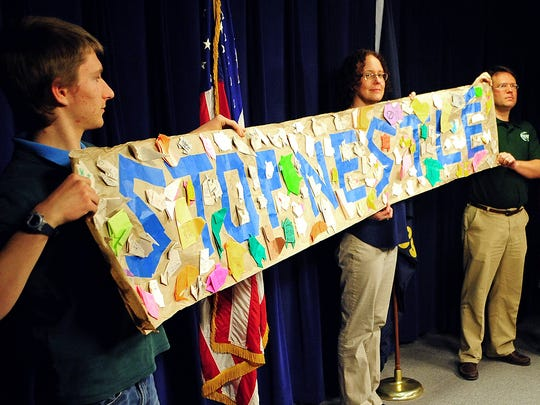 """A group opposed to a potential water deal with Nestlé Waters holds a """"Stop Nestlé"""" sign during a press conference May 14, 2015, at the Oregon State Capitol in Salem."""