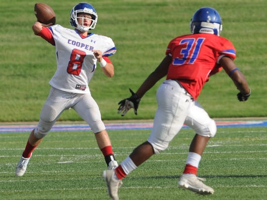 Cooper quarterback Henry Ferrel (8) gets ready to throw a pass as James Griffin (31) defends during the Cougars' annual Red & Blue spring football game in May.
