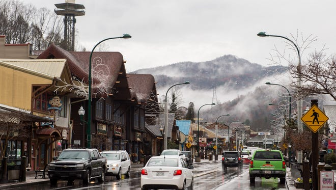 Rain falls as cars drive through downtown Gatlinburg, Tenn., Tuesday, Dec. 6, 2016.
