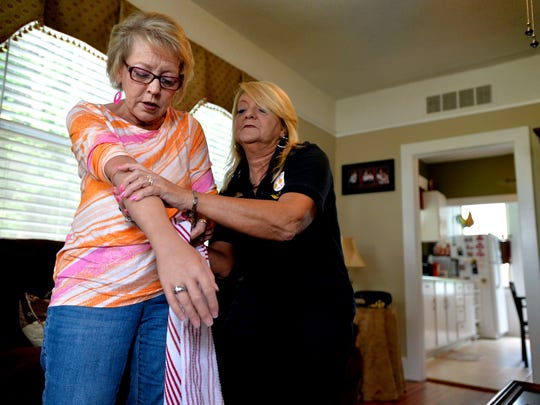 Pat Stephens, a survivor of domestic violence, puts on a prosthetic arm and is helped by younger sister Joy at their home in Lyman on Tuesday, May 12, 2015.