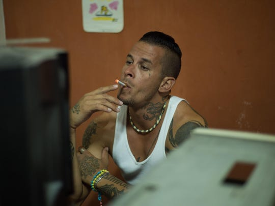Sitting behind speakers and computers in the underground rap studio, Adrian Espronceda takes a drag on his cigarette.