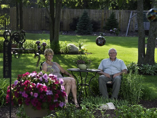 Darcy and Dan Zeleske sit in their expansive garden.
