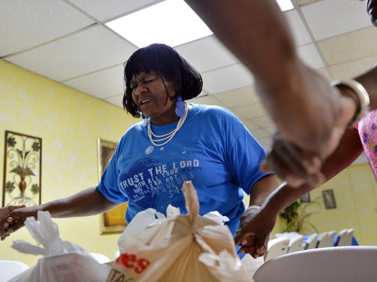 """Jeannie Simpson, founder and director of Extended Hands of Gods Servants at First Christian Fellowship Baptist in City View, prays alongside volunteers and a person receiving the church's services. """"We try to pray with every person that comes through here,"""" Simpson said."""
