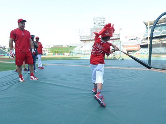 Thomas Walkup (right) takes a swing as Angels outfielder Mike Trout looks on.