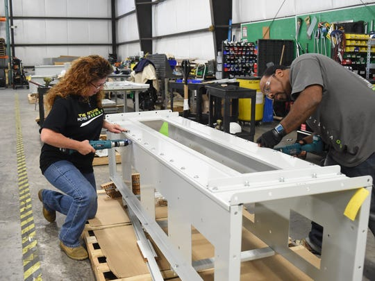 Joanne Carusillo, left, and Curtis Inocencio, right, assemblers at Nerak Systems, work on a product in the warehouse portion of the Fishkill office.