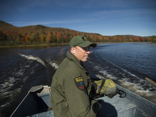 Ranger Jay Scott pilots a dinghy on Indian Lake to inspect campsites.