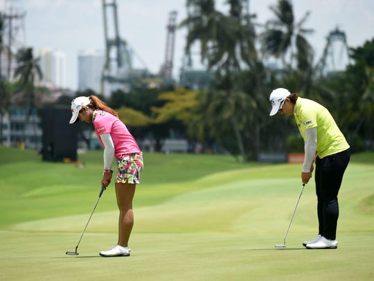 South Korea's Amy Yang, right, and Pornanong Phatlum of Thailand play on the 9th hole during the final round of the HSBC Women's Champions golf tournament at the Sentosa Golf Club in Singapore on March 6, 2016.