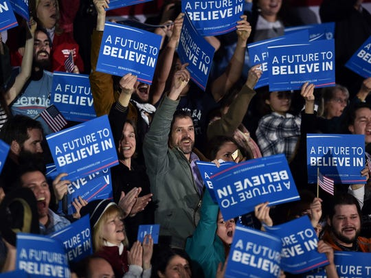 Supporters of US Democratic presidential candidate Bernie Sanders cheer as they watch a poll result on televison.