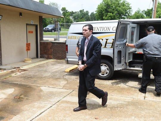 Nicholas Ian Roos, center, walks into the Baxter County
