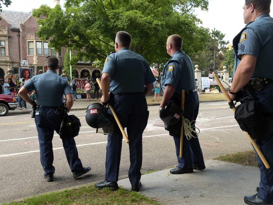 St. Paul police officers watch from across the street as protesters, encamped in front of the Governor's Residence on Summit Avenue in St. Paul, Minn. pack up their belongings on Tuesday, July 26, 2016. Police have arrested an unknown number of protesters in front of the governor's mansion on St. Paul's Summit Avenue. Demonstrators have been camping outside the governor's residence since early July 7, a day after the shooting of Philando Castile, who was killed by a St. Anthony police officer during a traffic stop. (Scott Takushi/Pioneer Press via AP)