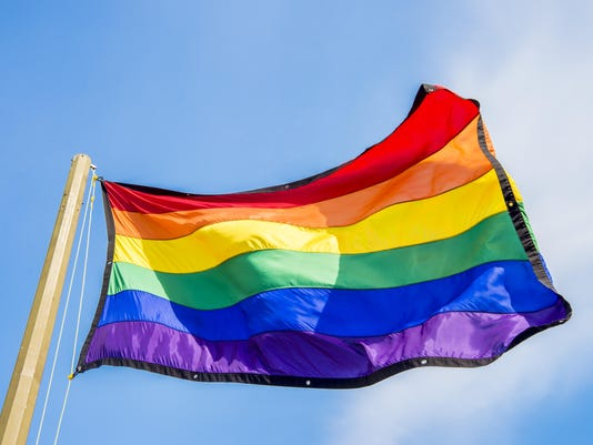 Gay rainbow flags waving over blue sky background