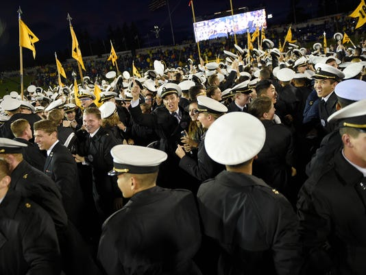 Navy midshipmen and fans storm the field and celebrate the 46-40 win over Houston after an NCAA football game, Saturday, Oct. 8, 2016, in Annapolis, Md. Navy won 46-40. (AP Photo/Nick Wass)