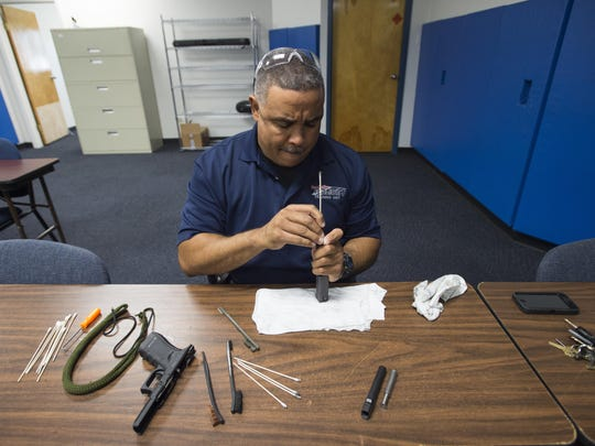Officer Al Brown cleans his weapon following a firearms exercise at the Fort Collins Police Services shooting range Sept. 27.