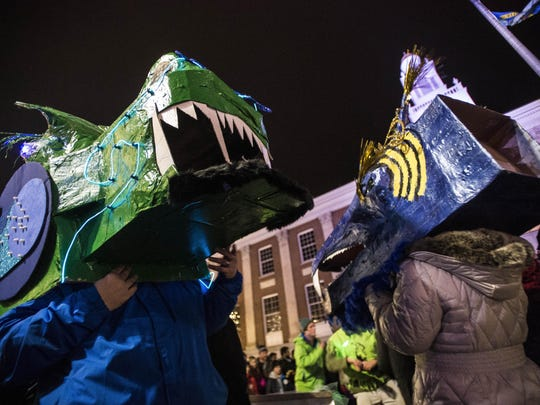 Newlyweds Dave Gerns, left, and Julie Longfellow of South Burlington parade as dragons on Church Street in downtown Burlington on New Year's Eve during the First Night Burlington parade.