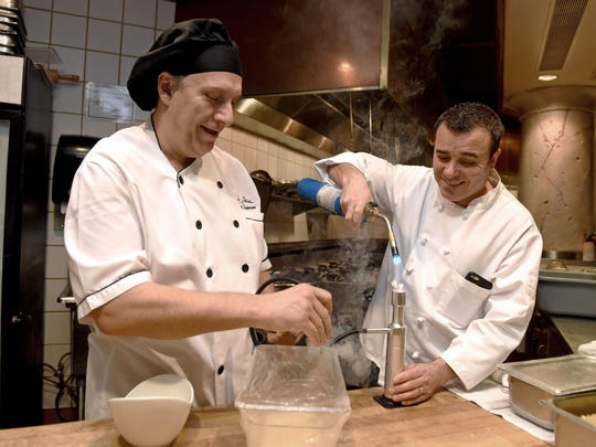 Together again: Eldorado executive chef Ivano Centemeri, left, and La Strada chef Massimo Riggio smoke lobster in the restaurant's kitchen. The two have worked together, on and off, for more than 20 years.