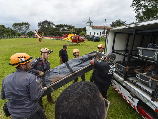 Military firefighters carry the corpse of a victim recovered from the mudslides areaon January 26, 2019 in Corrego do Feijao near the town of Brumadinho, Brazil.